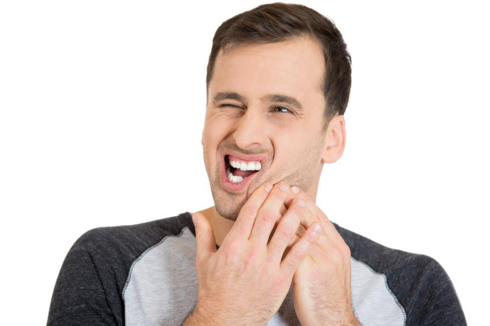 a man holds his hand to his mouth in pain | root canals st petersburg