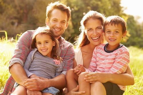 a family smiles in a meadow | st petersburg fl dental exams