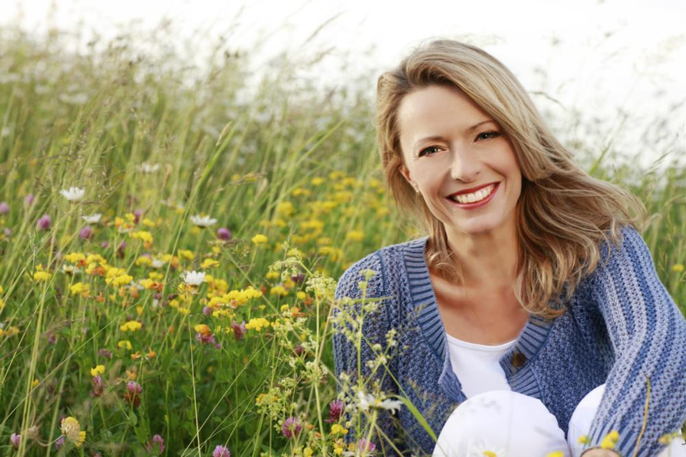 a woman smiles in a meadow | dentist st petersburg fl