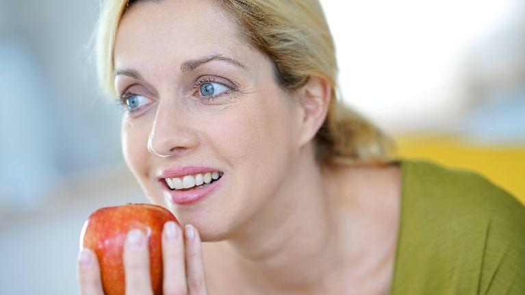 a woman goes to take a bite of an apple | dental crowns st petersburg fl