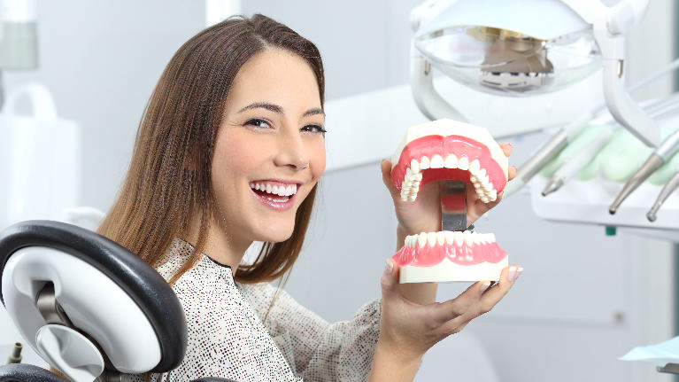 a woman holds a set of fake teeth | oral surgeon st petersburg